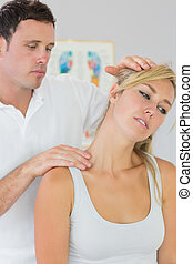 Good looking physiotherapist examining patients neck in...
