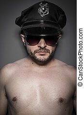 Good looking policeman, sexy police with sunglasses over dark background