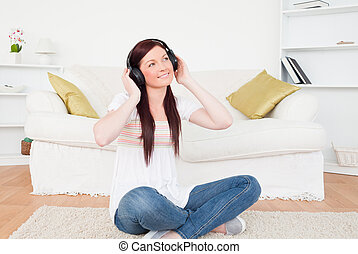 Good looking red-haired female listening to music with headphones while sitting on a carpet in the living room