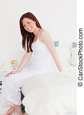 Good looking red-haired female posing while sitting on her bed