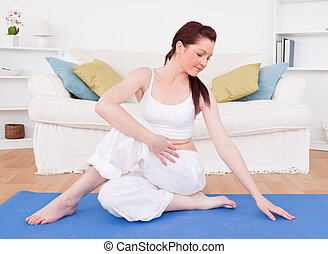 Good looking red-haired female stretching in the living room