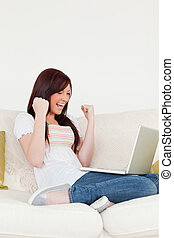 Good looking red-haired woman being joyful after gambling with her laptop while sitting on a sofa in the living room
