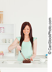 Good looking red-haired woman cutting some cake in the kitchen