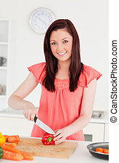 Good looking red-haired woman cutting some carrots in the kitchen