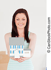 Good looking red-haired woman holding a miniature house while standing on the floor at home