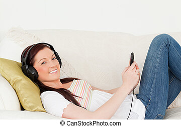 Good looking red-haired woman listening to music with headphones while lying on a sofa in the living room