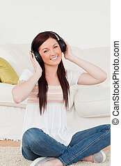 Good looking red-haired woman listening to music with headphones while sitting on a carpet in the living room