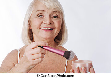 Good looking retired woman holding a makeup brush