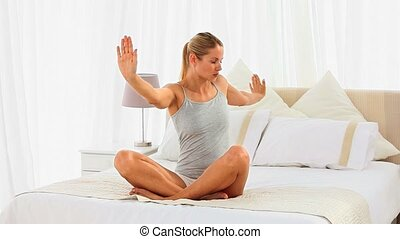 Good looking woman doing yoga on her bed