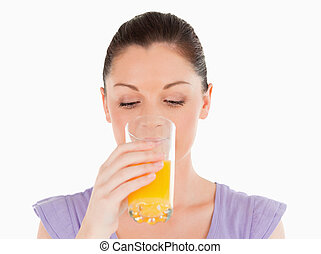 Good looking woman drinking a glass of orange juice while standing against a white background