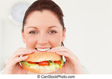 Good looking woman eating a sandwich for lunch