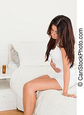 good looking woman having stomach ache in bedroom