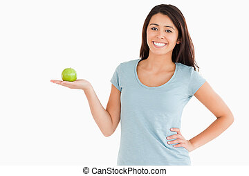 Good looking woman holding a green apple