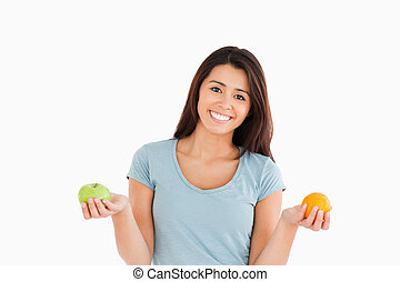 Good looking woman holding an apple and an orange