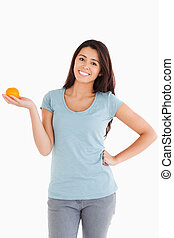 Good looking woman holding an orange
