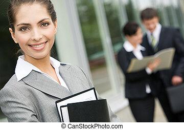Image of good-looking businesswoman in grey suit outdoor