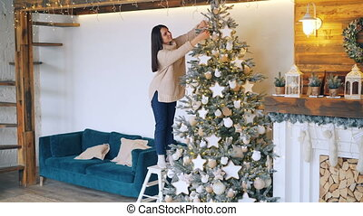 Good-looking woman is decorating fir-tree for Christmas holidays putting decorations balls and stars on branches. Beautiful lights and fireplace are visible.
