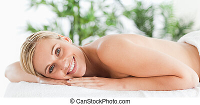 Good looking woman relaxing on a lounger in a wellness ...