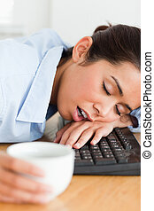 Good looking woman sleeping on a keyboard while holding a...