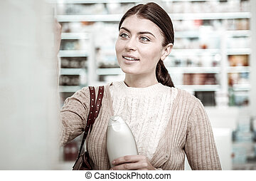 Good-looking woman smiling while shopping in pharmacy store on weekend