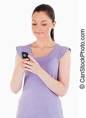 Good looking woman writing a text on her phone while standing