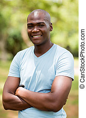 young african man with arms crossed outdoors