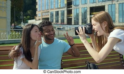 Good looking young girl taking photos of lovely couple -...