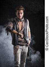 Good Looking Young Man in Pirate Fashion Outfit on Black Background with Smoke. Captured in Studio.