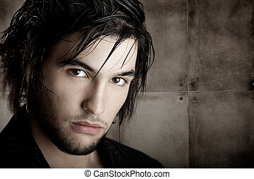 Good looking young man with modern Hair Style over a grunge wall background