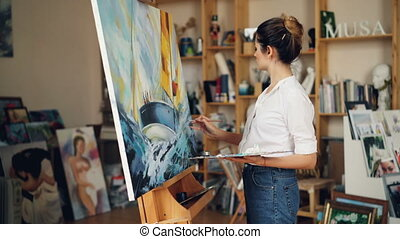 Good-looking young woman in casual clothing is painting in...