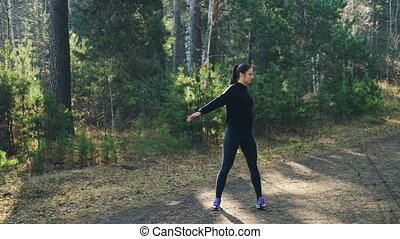Good-looking young woman in modern tracksuit is exercising...