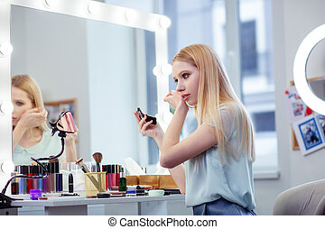 Good looking young woman showing makeup lesson