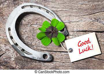 Horseshoe, Leafed clover and tag with good luck on wooden board