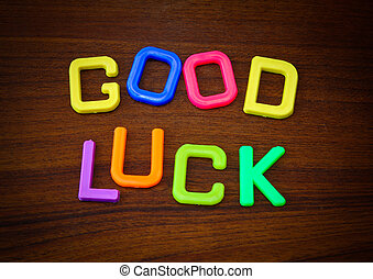 Good luck in colorful toy letters on wood background