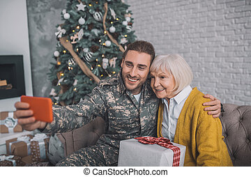 Smiling man in camouflage uniform making selfie with mom
