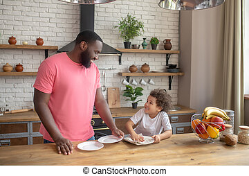 Tall dark-skinned man in a pink tshirt standing and smiling , while his kid wiping the plate