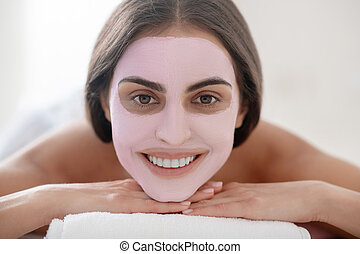 Young pretty woman with mask on her face smiling positively