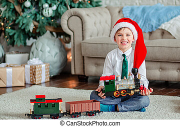 Good morning. Happy little boy with a gift, toy train, under the Christmas tree on New Year's morning. Time to fulfill wishes.