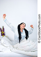 Good morning - Happy woman waking and stretching hands in ...