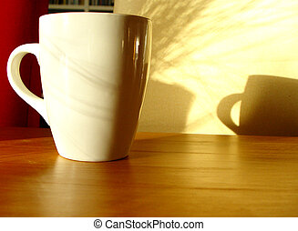 mug on a wooden table with morning shadows in background