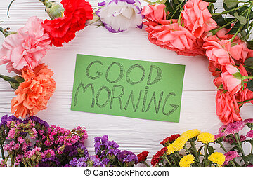 Good morning note amoung different flowers.