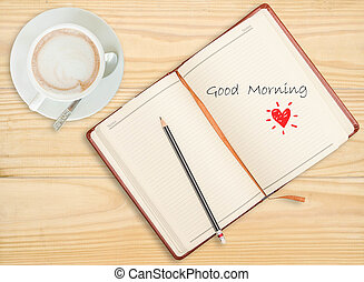 """""""Good morning"""" on notebook with pencil and coffee cup on wooden"""
