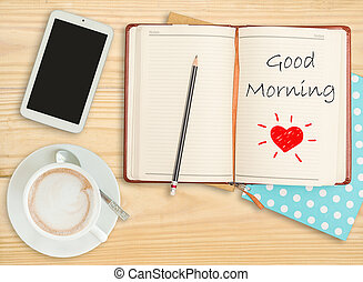 Good morning on notebook with pencil, smart phone and coffee cup