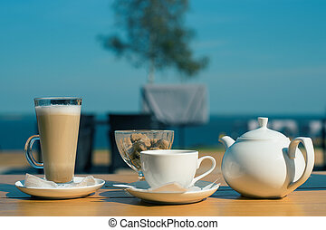Good morning. set of latte mugs, a Cup of tea and a teapot with cane sugar on the summer terrace of the cafe