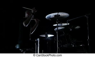 Good music in the perfomance of a professional drummer. Side view. Black background. Slow motion