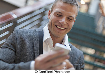 Good news! Men reading sms on smartphone in business...