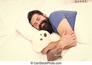 Good night. Sleep well. Sweet dreams. Bearded hipster play toy. Valentines day gift. Man sleep hug soft toy relaxing in bed. Cute teddy bear toy. Softness tenderness. Playful adult fall asleep