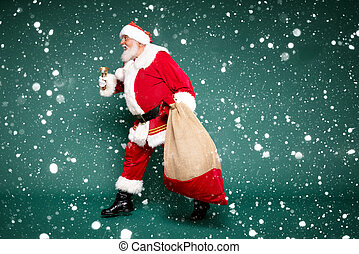 Good old Santa Claus carrying gifts in a big sack.