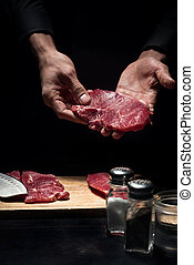Close up of chefs hands holding meat