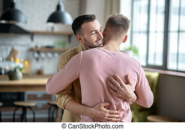 Two young men standing and hugging each other